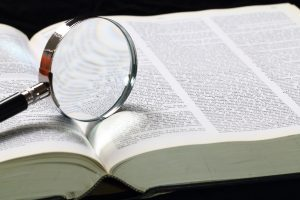 Dictionary with an magnifying glass on top