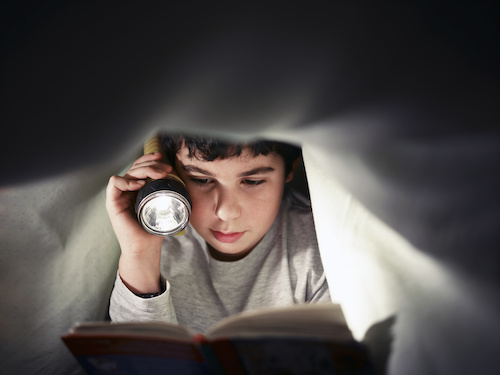 a boy reading a book under covers at night